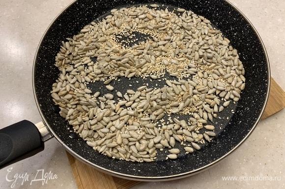 Семена подсолнуха и кунжута слегка подсушить в духовке или на сковороде. Изюм замочить в воде на несколько минут, затем отжать.