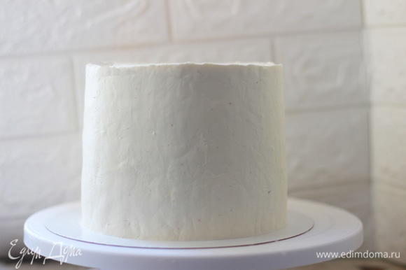 Отделка. Сыр вынуть за 20 минут до приготовления крема. В дежу положить сыр, пудру и сливки, взбить 3 минуты до полного соединения. Далее крем вымешать лопаткой для избавления от пузырей воздуха. Заготовку вынуть из формы, взять немного крема и сделать черновую обмазку торта. Это необходимый этап. Таким образом вы заполняете пустоты, слегка выравниваете корж и собираете кремом крошки от бисквита с боков. Иначе при чистовой сборке они будут перемешиваться с кремом и распределяться по всех поверхности. Поставить торт в холод на полчаса, крем за это время хорошо схватится, и выравнивать будет легче. Уложить крем в мешок (или просто наносить спатулой) и равномерно нанести по всей поверхности торта. Выровнять с помощью кондитерского шпателя или просто школьным уголком. Для качественного выравнивания нужен поворотный столик и навык работы с кремом.