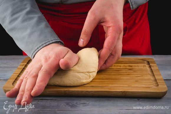 Разомните подошедшее тесто, разделите на две части.