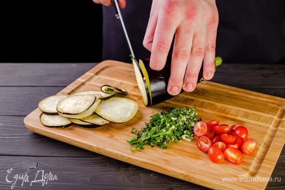Баклажаны нарежьте тонкими кружочками, помидоры черри разрежьте пополам. Измельчите чеснок и зелень.
