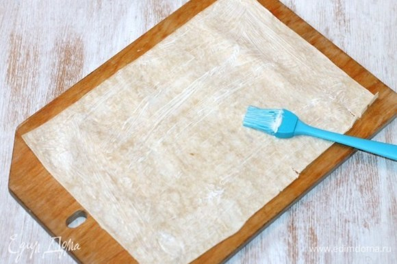 Разложить лист лаваша (66х46 см) на разделочной доске и разделить его пополам (33х23 см). Смазать лаваш домашним майонезом. Болгарский перец запечь в духовке и удалить семя и шкурку.