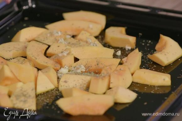 Выложить тыкву с чесноком на противень, приправить сухими травами, полить небольшим количеством оливкового масла, посолить и поперчить. Убрать в духовку на 10 минут.