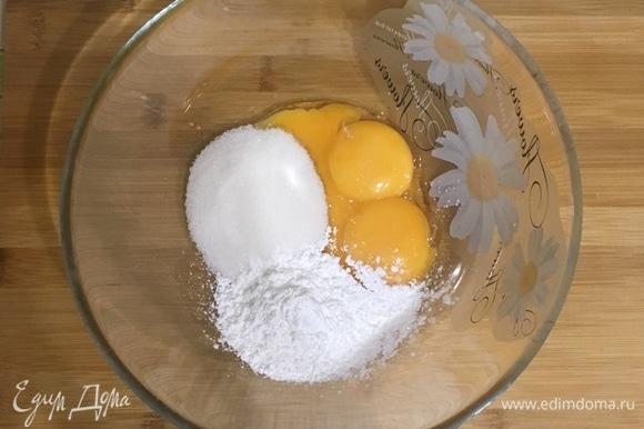 В отдельной миске смешайте желтки, сахар и крахмал. Влейте горячее молоко в желтки, интенсивно мешая венчиком.