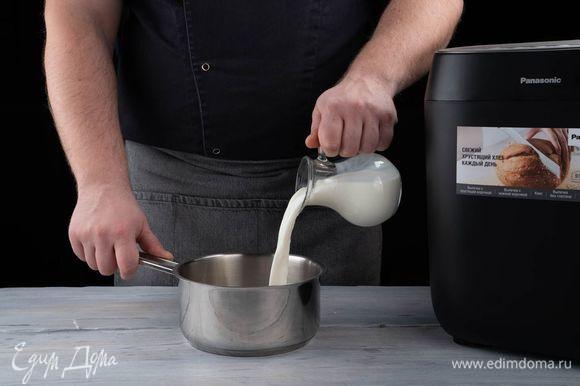Небольшими порциями влейте молоко, все перемешайте. Поставьте сотейник на огонь, доведите смесь до кипения.