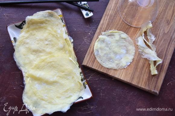 Из яичной заготовки вырезать круг диаметром меньше, чем получившиеся четвертинки листа нори.