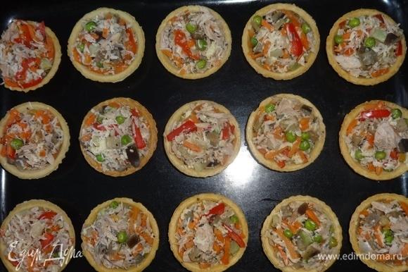 Начинить тарталетки рыбно-овощной смесью, выложить на противень и поставить в духовку, разогретую до 180°C, на 5–7 минут. Зеленый лук вымыть, обсушить, мелко нарезать.