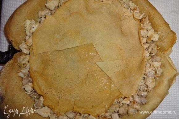 На сыр положить 2 блинчика, один из которых оставить целым, а второй разрезать на части, чтобы закрыть курицу (края надрезать, чтобы получились бортики).