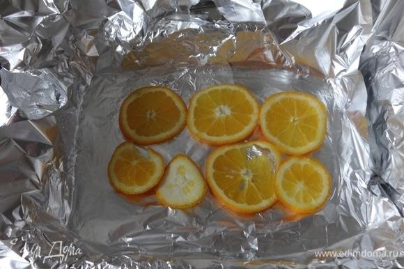 Фольгу кладем в форму в 3 слоя. Выложить половину кружков апельсинов.