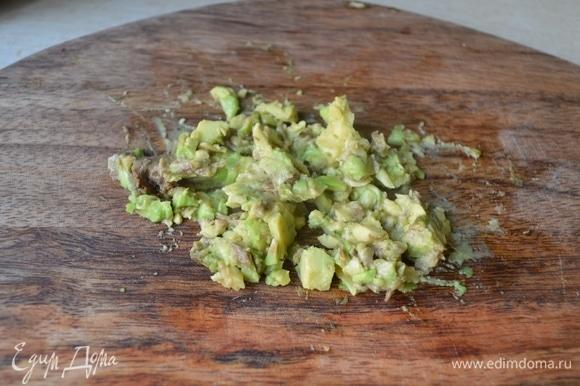 Измельчить авокадо, добавить к рыбе и луку.