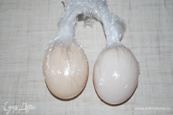 Тщательно вымойте два куриных яйца, оберните их пищевой пленкой.
