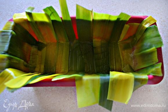 У лука-порея отрежьте зеленую часть, аккуратно раскройте и бланшируйте в кипящей, слегка подсоленной воде 1–2 минуты, после чего тут же охладите ледяной водой. Просушите листья порея с помощью бумажного полотенца и выложите в смазанную растительным маслом форму для кекса (края должны немного свисать).
