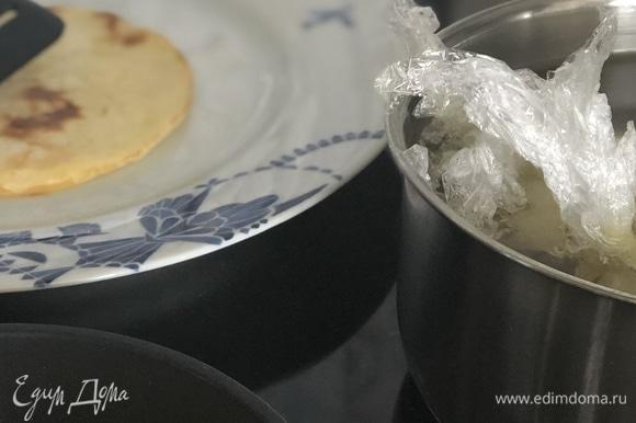 Варим яйцо пашот. Пищевой пленкой нужно выстелить неглубокую чашку, обязательно смазать пленку растительным маслом (иначе белок прилипнет к ней). Аккуратно разбить внутрь 1 яйцо, посолить и поперчить по вкусу, затем собрать края пленки и завязать ниткой. Такой мешочек поместить в кастрюлю с кипящей водой на 3–4 минуты. Затем хвостик пакета отрезать ножницами и яйцо аккуратно достать.