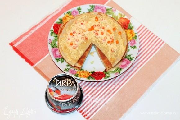 Смазываем каждый блин, мягким плавленым сыром и распределяем по 1 ч. л. красной икры.