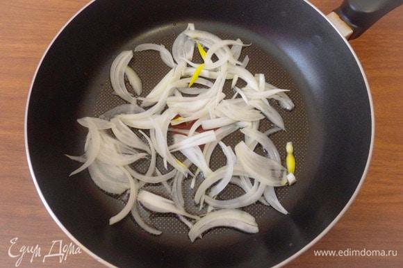 Разогреть в другой сковороде ложку растительного масла. Репчатый лук нарезать тонкими перьями, выложить лук в сковороду, добавить половину чайной ложки сахарного песка и припустить лук до прозрачности.