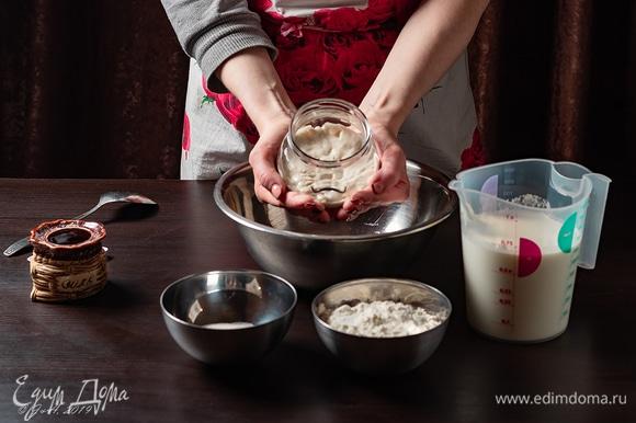 Для блинов нам потребуются пшеничная закваска, мука, теплое молоко, сахар и соль. Сначала мы вырастим пшеничную закваску. Это довольно несложно, просто требует времени и соблюдения некоторых условий. Нам потребуется 25 г муки пшеничной и 25 г воды. Воду берите либо отстоявшуюся, либо фильтрованную, на крайний случай — холодную из-под крана, но ни в коем случае не кипяченую. Скорость роста закваски не зависит от количества ингредиентов, я просто делала «на пробу», а вы можете сделать побольше, тогда просто возьмите столько, сколько хотите, главное, чтобы в одинаковом количестве. Смешайте так, чтобы не было комочков, положите в стеклянную банку и плотно закройте крышкой. Капроновой или винтовой — без разницы. Будущую закваску отправьте в теплое место приблизительно на сутки. Температура около 28°C. Сразу оговорюсь: вариантов может быть несколько, я делала так, как меня учила знакомая, у которой большой опыт выпечки на закваске. Поэтому ознакомиться с какими-то нюансами, почитать дополнительный материал можно и нужно, потому что это затягивает, раз попробуешь, и понеслось… Примерно через сутки масса пойдет пузырями, разжижится, увеличится в объеме и приобретет специфический запах. Не следует пугаться, все идет по плану. У нас начались процессы брожения. Теперь нам надо ее покормить. Содержимое банки слегка перемешать, отделить 25 г (я пользуюсь весами). Остаток залить кипятком, слить, тщательно вымыть банку (без использования средств, просто водой), высушить. В закваску долить 25 г воды и положить 25 г муки пшеничной. Тщательно размешать. Тесто должно быть нежидким и в идеале тянуться ниточками при размешивании. Не замешивайте очень круто — наши бактерии еще слабенькие и могут не справиться с работой и задохнуться. Также не надо разводить жидко, иначе бактериям в стадии активного роста будет нечего есть, и закваска не будет расти. Так что количество муки может быть и чуть больше, и чуть меньше, но 1:1 — это классика. Снова поставьте в теплое место, пока до утра. Поздра