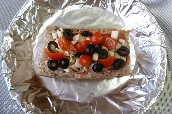 Нарезать шампиньоны небольшими кубиками, помидоры —дольками, маслины — колечками. Заполнить хлебную основу.