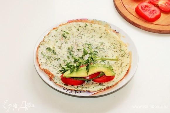 Готовые омлеты выложить на тарелки, сверху разложить нарезанное авокадо, помидоры и оставшиеся листья петрушки, посолить, поперчить.