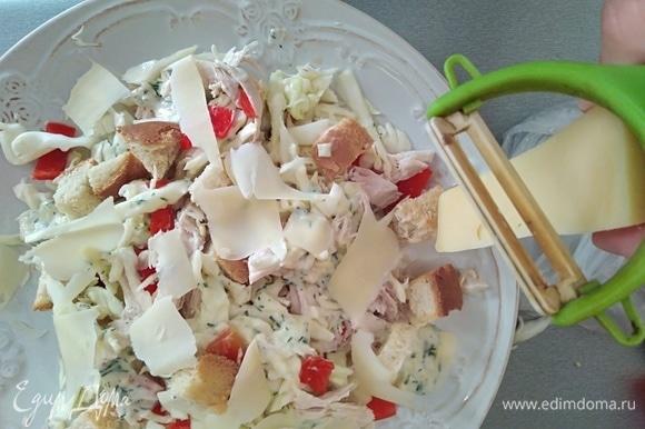 Заправить салат. Сверху разложить сухарики и тертый сыр.