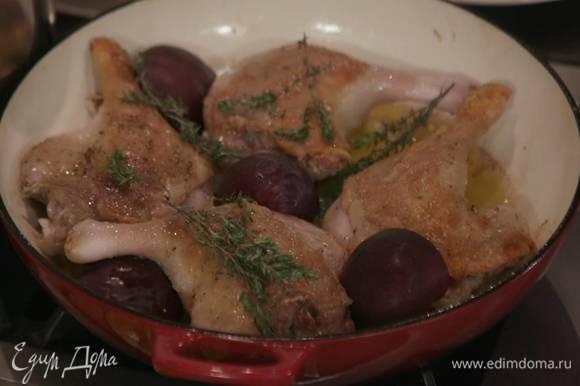 К обжаренным ножкам добавить половину слив и веточки тимьяна, накрыть жаропрочной крышкой и запекать в разогретой духовке около часа.