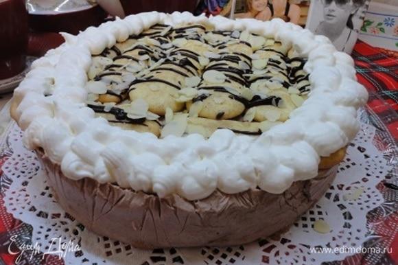 Застывший торт освобождаем от формы и пленки. Поливаем шоколадом, посыпаем миндальными лепестками и украшаем взбитыми в крепкую пену сливками.