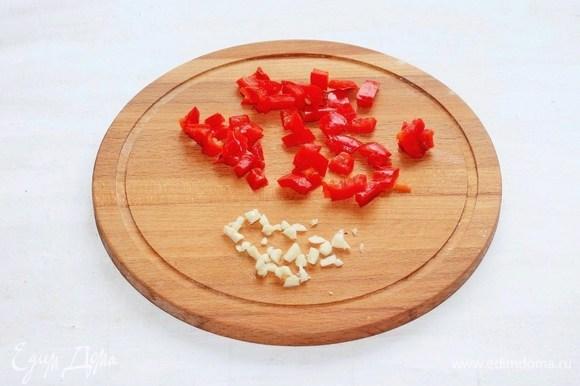 Чеснок почистить, раздавить плоской стороной ножа и мелко порубить. Сладкий перец нарезать маленькими кубиками, удалив семена.