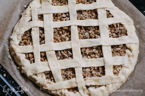 Оставшееся тесто тонко раскатать, нарезать полосками и украсить пирог. Желток соединить с 1 ст. л. молока, посолить, перемешать и смазать пирог. Выпекать в заранее разогретой до 200°C духовке 15–18 минут.
