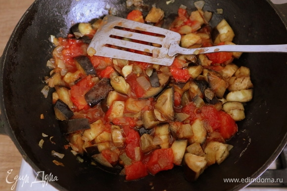 Промыть баклажаны, просушить бумажным полотенцем и отправить на сковороду. Готовить, помешивая, 3–5 минут, затем добавить помидоры и сахар, убавить огонь и тушить на медленном огне еще несколько минут до готовности баклажанов.
