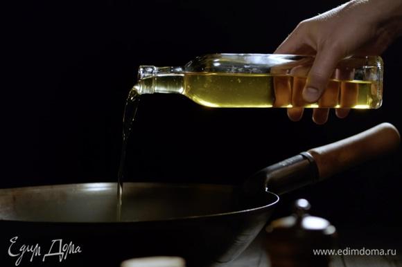 Разогреваем в воке оливковое масло.