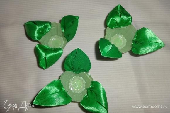 Из зеленой атласной ленты сделать листья и приклеить их в 3 круглые ячейки.