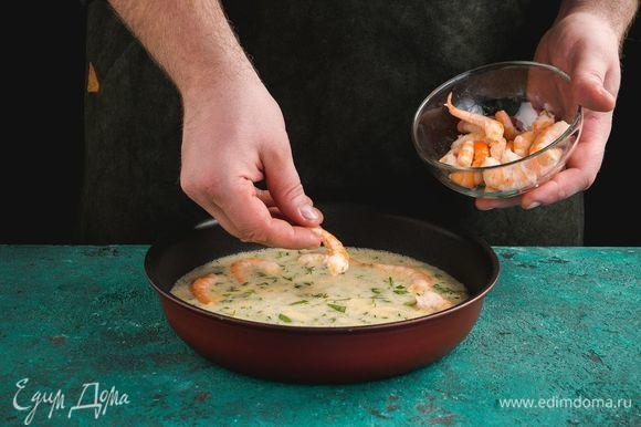 Форму для выпекания смажьте сливочным маслом. Выложите яичную смесь. Добавьте очищенные креветки.