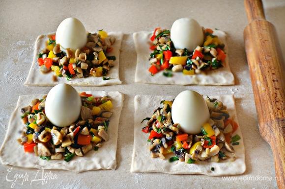 Тесто разморозьте и раскатайте на посыпанной мукой поверхности в тонкий пласт. Разрежьте тесто на 4 квадрата со стороной 10–12 см). В центр каждого положите по 2 ст. л. с горкой начинки, сверху аккуратно установите вареное яйцо.