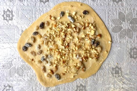 Раскатать каждую часть на припыленной мукой поверхности. Смазать размягченным сливочным маслом и распределить порубленные орехи и изюм.