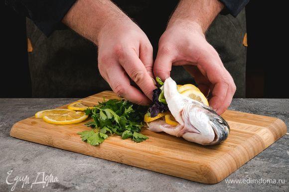 Сделайте несколько диагональных разрезов по бокам рыбы, вложите в них кружочки нарезанного лимона. Также нафаршируйте дораду лимоном и зеленью.