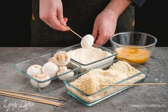 В отдельные емкости высыпьте панировочные сухари и муку. Шампиньоны окуните в яичную смесь, затем обваляйте в муке, затем еще раз окуните в яичную смесь и потом обваляйте в панировочных сухарях.