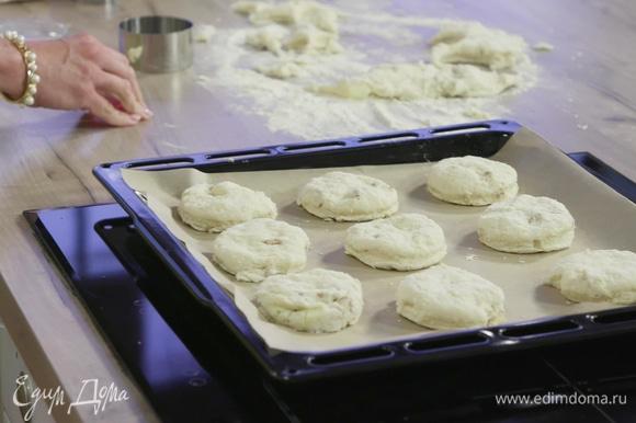 Вырезать при помощи кулинарного кольца булочки и выложить их на противень, покрытый бумагой для выпекания.