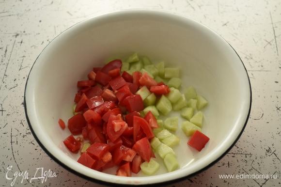 Огурцы очистить и нарезать кубиками. Нарезать помидоры. Выложить овощи в большую миску.