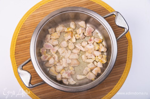 Разогреть сотейник с маслом для жарки. Обжаривать кусочки курицы 5 минут на среднем огне. Добавить куркуму, мелко порубленный чеснок (1 зубчик), соль, свежемолотый перец по вкусу.