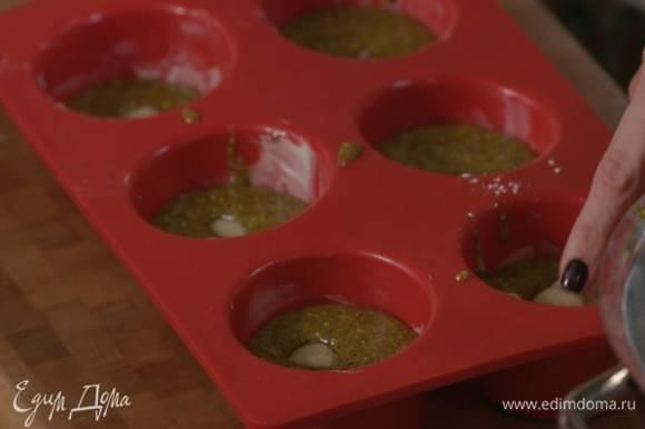 Формочки для маффинов смазать оставшимся сливочным маслом, выложить тесто, сверху поместить марципановые шарики и утопить их.