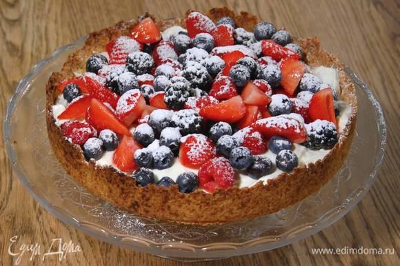 На остывший корж равномерно выложить сливочный крем, сверху разложить ягоды, посыпать все оставшейся сахарной пудрой.