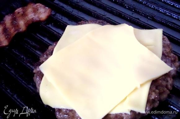 Когда котлета обжарится снизу, перевернуть и сразу положить 2 пластинки сыра. Жарить снизу дальше.