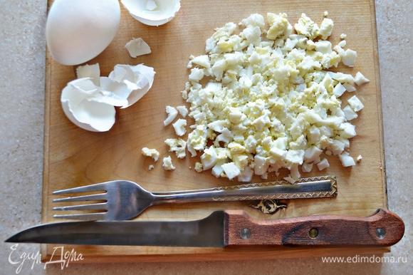 Отварите яйца мелко порубите и разомните немного вилкой. Яйца соедините с майонезом, слегка посолите, приправьте перцем и перемешайте.