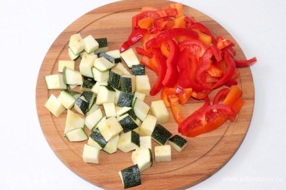 Очищаем болгарский перец от семян и нарезаем соломкой. У цукини (или кабачка) отрезаем плодоножку и огрубевшую мякоть с верхушки, нарезаем кубиками.