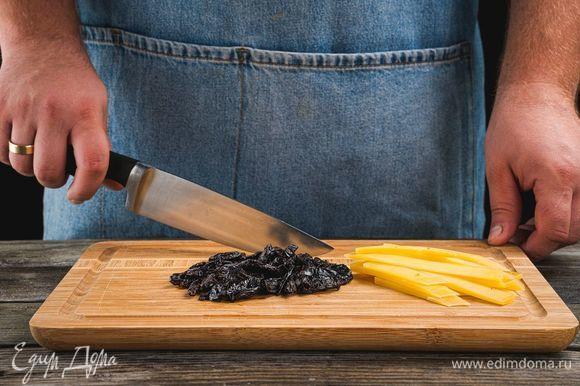 Нарежьте чернослив и сыр.