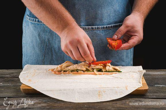 Каждый лист лаваша разрежьте пополам, смажьте соусом. Выложите на один край лаваша нарезанные огурцы, обжаренное куриное филе и помидоры.