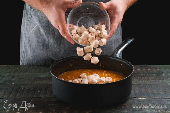 Положите нарезанные колбаски в сковороду, посолите, поперчите. Добавьте лавровый лист, чеснок и измельченную зелень петрушки. Тушите колбаски с фасолью еще 3 минуты и снимайте с огня.