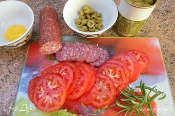 Помидоры, салями и оливки нарежьте кружочками. Включите духовку на разогрев до 200°C.
