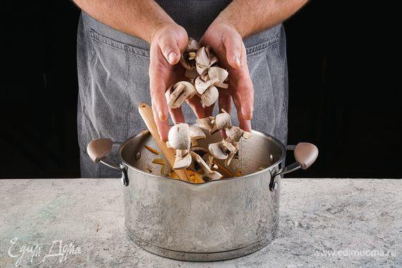 Туда же добавьте тщательно промытые и нарезанные грибы. Обжарьте 7 минут.