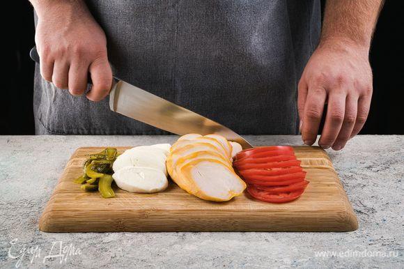 Копченую куриную грудку наредьте пластинами. Огурцы нарежьте слайсами, моцареллу и помидор нарежьте кружочками.