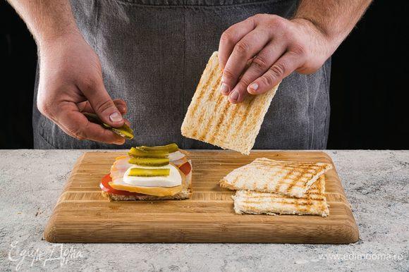 На один кусочек выложите листья салата, грудку, моцареллу, огурцы. Накройте сверху еще одним тостом и разрежьте по диагонали напополам.