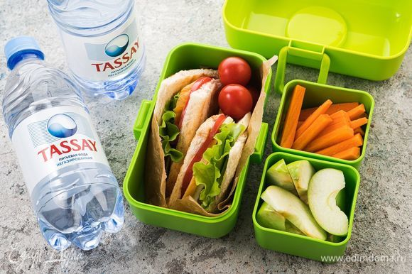 Положите сэндвичи в контейнер, добавьте бутылку негазированной воды Tassay и контейнеры с морковными палочками и кусочками яблок — питательная и сытная ссобой для ребенка готова!